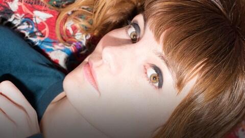 Halo Maud (Maud Nadal), regarde l'objectif, couchée sur une couverture multicolore.