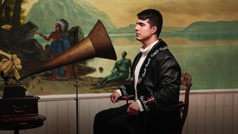 Un homme assis et faisant face à la corne d'un vieux gramophone