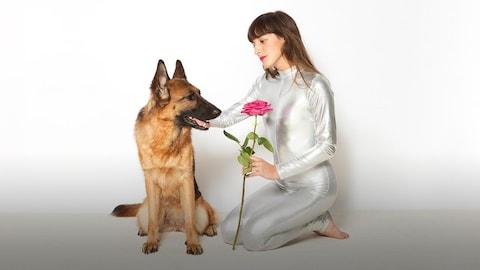 La chanteuse Juliette Armanet qui tend une rose à un chien.