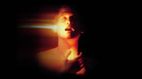 Image d'un homme, vu à partir du haut des épaules, les yeux fermés tournés vers le haut, la bouche ouverte en extase, baigné de lumière chaude orangée, un rayon de lumière sortant de son oreille droite.