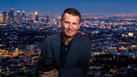 L'animateur pose, ses écouteurs à la main. En arrière-plan, on voit une photo de la ville de nuit, qui s'étend jusqu'à la lligne d'horizon.