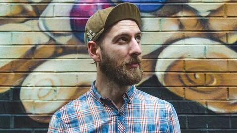 Maxime Auguste, devant un mur couvert de graffitis