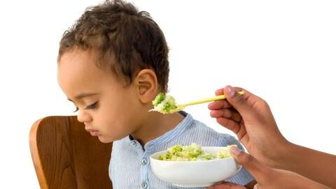 Un jeune enfant refuse la cuillère de nourriture qui lui est tendue.