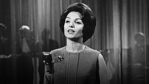 La chanteuse chantant devant un micro sur pied, dans un studio de Radio-Canada.