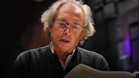 Le chef d'orchestre Philippe Herreweghe, cheveux gris épars, avec des lunettes, petites et ovales, regardant une partition