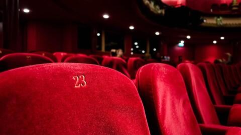 Image de rangées de sièges de velours rouge à l'intérieur d'un théâtre