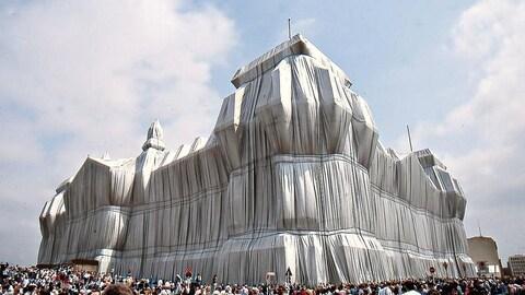 Extérieur. Jour. Le monument allemand est totalement emballé de toile blanche. Des gens se sont massés autour pour observer.
