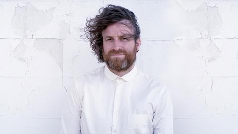 Simon Laganière en chemise blanche se tient cheveux au vent devant un mur de pierres peint en blanc.