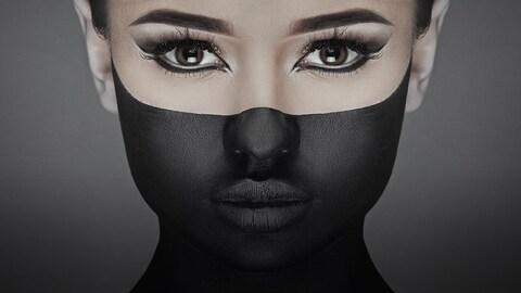 Visage d'une jeune femme dont la moitié inférieure est maquillée en noir.