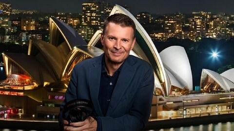 L'animateur pose pour la caméra, souriant. Derrière lui, on voit une photo de l'extravagante Maison de l'opéra et du centre-ville de Sydney.