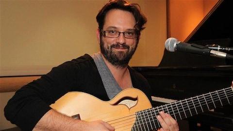 Un homme tenant une guitare devant un piano