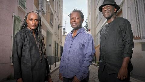 Les trois membres de la formation Bondeko (Richard Bona, Gerald Toto et Lokua Kanza) à l'extérieur dans une rue étroite.