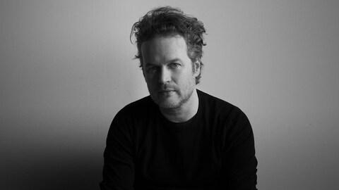 Photo noir et blanc. Tristan Malavoy, chandail noir, devant un mur de couleur claire.