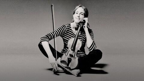 Vilde Frang, assise jambes croisées, tenant un violon verticalement sur ses pieds
