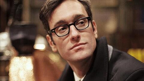 Le chanteur David Myles, vêtu d'une chemise noire, portant ses lunettes et regardant au loin
