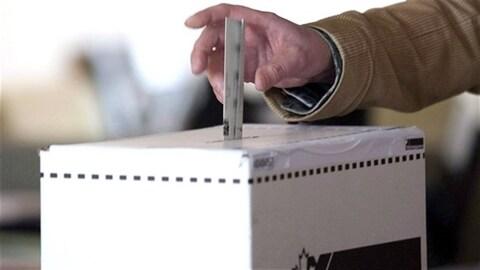 Une personne insère son bulletin de vote