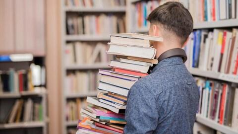 Un jeune homme vu de dos, portant de nombreux livres en équilibre, dans une bibliothèque.
