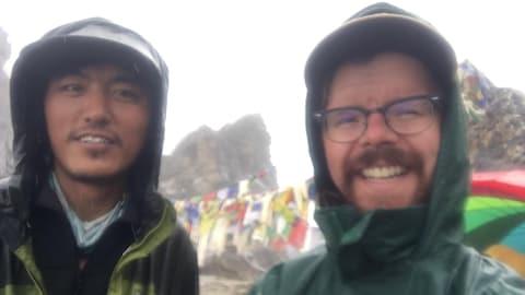 Les deux hommes souriants, vêtus d'imperméables, posent avec en arrière-plan un campement pour alpinistes.