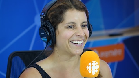 Anaïs Favron derrière un micro dans un studio radio de Radio-Canada.