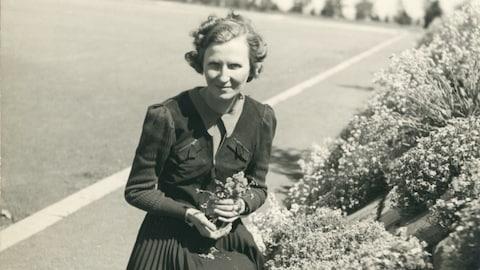 Marcelle Gauvreau cueille un bouquet de fleurs.