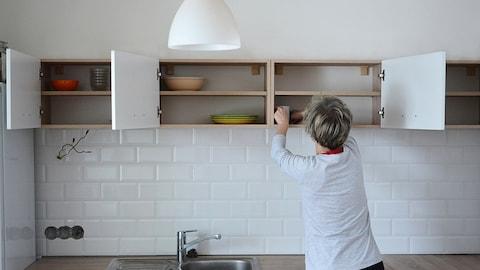 Une personne nettoie et range des armoires de cuisine.