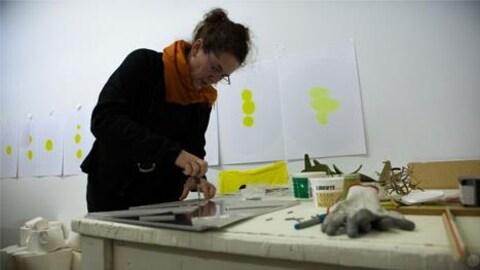 L'artiste en arts visuels, Hélène Rochette, travaille sur une oeuvre.