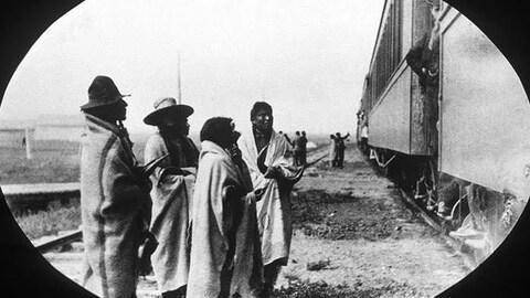 Quatre Autochtones enveloppés dans des couvertures regardent un train.