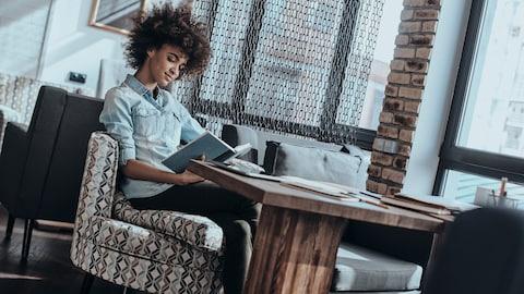 Une personne lit un livre dans un café.