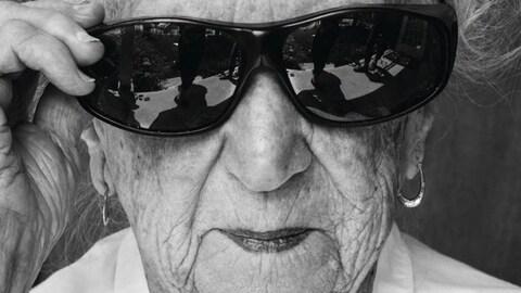 Une femme centenaire porte des lunettes de soleil