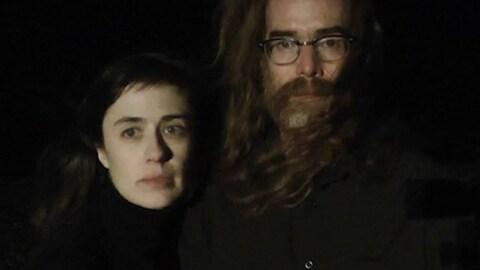 Le duo composé de Colleen Collins et David Trenaman habillés en noir sur un fond noir.