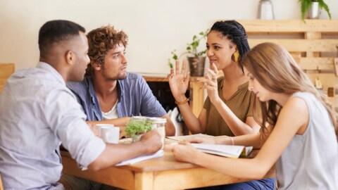 Quatre personnes discutent autour d'une table.