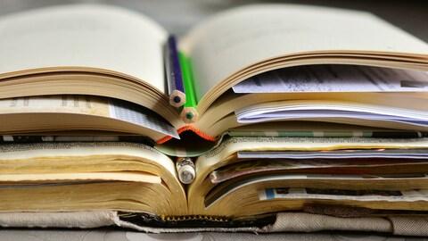 Gros plan de livres ouverts empilés avec des crayons et des feuilles glissées à l'intérieur de ceux-ci.