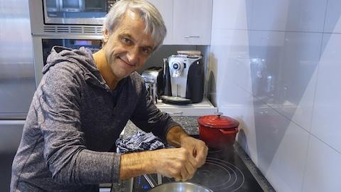 jean Soulard émiette du cannabis lors de la préparation d'un repas
