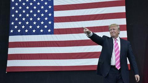 Le président Donald Trump devant un immense drapeau américain