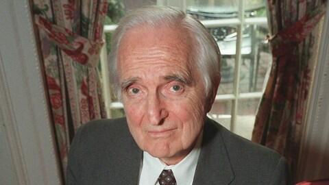 Une photo d'archives de Douglas Engelbart. Sur cette photo, il a les cheveux blancs et porte un complet gris, une chemise blanche et une cravate foncée.