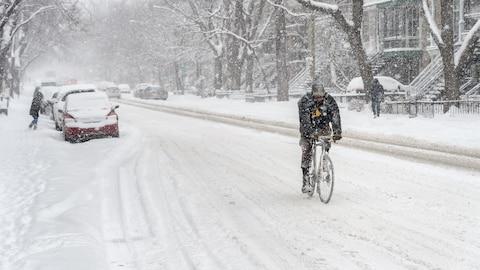 Un homme fait du vélo l'hiver à Montréal.