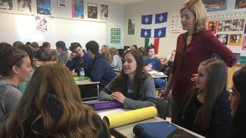 Des jeunes adolescents sont assis dans leur salle de classe et discutent en compagnie de leur enseignante de français.