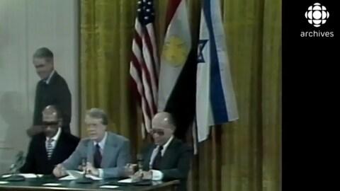 Les présidents Sadate et Carter, qu'accompagne le premier ministre Begin,  sont assis devant les drapeaux américain, égyptien et américain, pour signer les accords de Camp David.