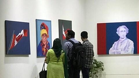 Trois personnes devant des œuvres de Charles Pachter