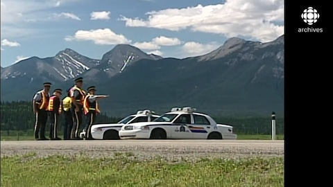 Une patrouille de policiers surveille une route que surplombent les montagnes rocheuses.