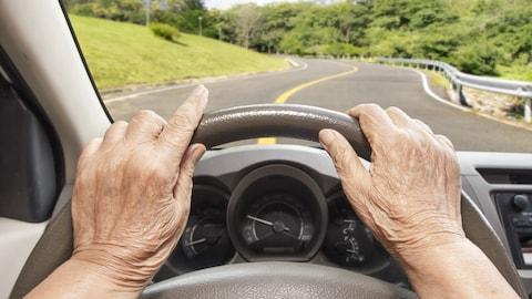 Une personne âgée circule en voiture sur une route.