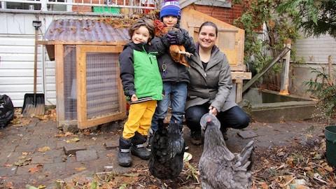 Louise Hénault-Éthier pose avec ses garçons Félix et Léo. Le trio est entouré des poules Brune, Noire et Grise.