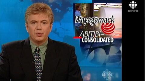 L'animateur Michel Viens présente le Téléjournal.  Derrière lui, on voit une mortaise avec les mots Wayagamack et Abitibi-Consolidated.
