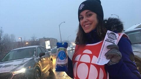 Une femme qui récolte des dons à une intersection routière