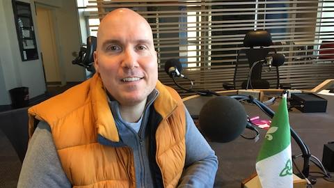L'historien Guillaume Teasdale est assis dans un studio de radio à Windsor, Ontario.