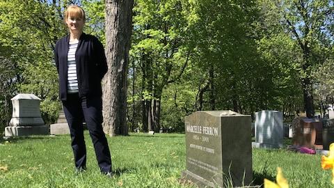 La directrice des programmes du patrimoine au Cimetière Mont-Royal de Montréal, Myriam Cloutier, devant la pierre tombale de la peintre Marcelle Ferron