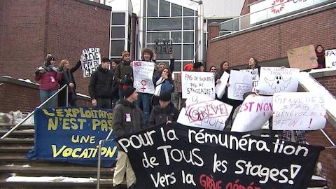 Des étudiants brandissent des affiches devant le Cégep du Vieux Montréal.