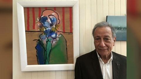 Jean-Baptiste Sercq devant le portrait que l'artiste Yvon Gallant a fait de lui.