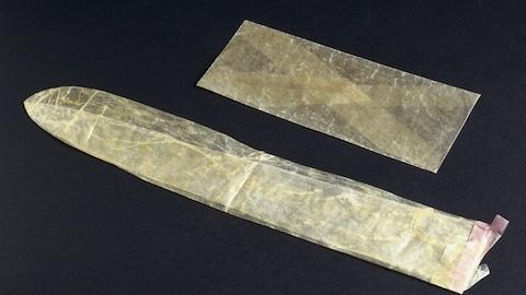 Un condom en lin est déposé sur une surface noire à côté d'une enveloppe.