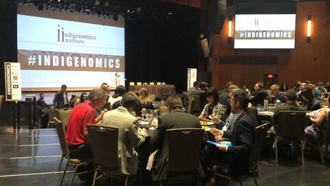 Salle où l'on voit plusieurs grandes tables rondes avec des gens qui mangent et qui assistent à une conférence du Indigenomics Institute.